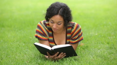 Young woman laying in grass reading book Stock Footage