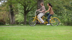 Couple having fun on tandem bicycle - stock footage