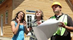Contractor and couple look at home plans Stock Footage