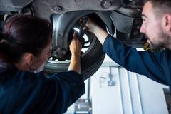 Mechanics examining car tyre using flashlight Stock Photos