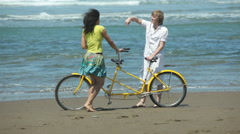Couple at beach with tandem bicycle - stock footage