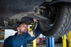 Mechanic examining car tyre using flashlight Stock Photos