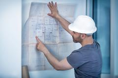 Architect builder studying layout plan of the rooms - stock photo
