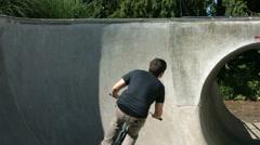 BMX biker rides skate park bowl, slow motion Stock Footage