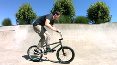 BMX rider spins handlebars, slow motion Stock Footage