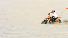 Man riding a motorcycle in sand, slow motion Stock Footage
