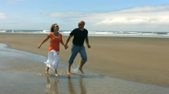 Couple run on beach together, slow motion speed ramp Stock Footage