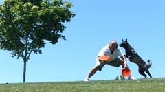 Dog jumps of woman's back and catches frisbee, slow motion Stock Footage