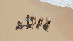 Family writes ALOHA in sand at beach - stock footage