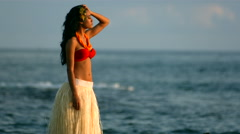 Polynesian woman stands by ocean waves Stock Footage