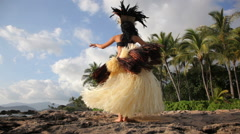 Polynesian dancer performs along rocky coastline Stock Footage