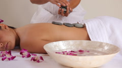 Woman gets hot stone spa treatment Stock Footage