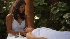 Woman gets massage at tropical resort spa Stock Footage