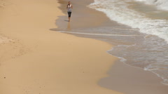 Woman jogging on beach, high angle view Stock Footage
