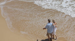 Senior couple walking together on beach, high angle view - stock footage