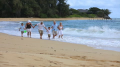 Multi-generation family walking together at beach - stock footage