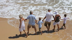 Multi-generation family running on beach together - stock footage