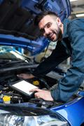 Mechanic using a diagnostic tool Stock Photos