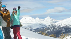 Four snowboarders look out from mountain top Stock Footage