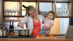 Mother with baby in kitchen multi-tasking Stock Footage
