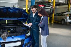Mechanic showing the quotation to a customer Stock Photos