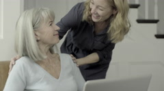 Senior Adult female looking at laptop with mature daughter - stock footage