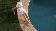 Woman sitting by pool at tropical resort Stock Footage