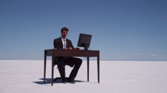 Businessman and businesswoman at salt flat with office desk Stock Footage