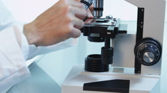 Asian scientist looks into microscope Stock Footage