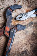 Adjustable spanner and pliers on wooden plank Stock Photos