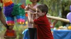 Boy hitting a pinata at party, slow motion Stock Footage