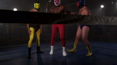 Three masked wrestlers stand in ring Stock Footage