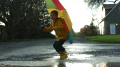 Young boy jumping in puddles with umbrella, slow motion - stock footage