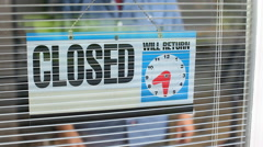 Business owner puts open sign in window Stock Footage