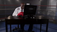 Businessman with desk in boxing ring, punching computer screen Arkistovideo