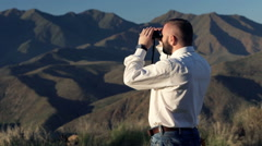 Young businessman looking at land through binoculars in country Stock Footage