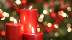 Burning candles, with Christmas tree in background Stock Footage
