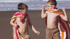 Young boys at beach flexing muscles with superhero costume Stock Footage