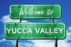 yucca valley vintage green road sign with blue sky background - stock illustration