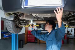 Mechanic examining car using flashlight Stock Photos