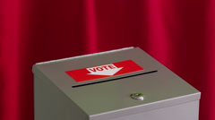 Hand puts vote into ballot box Stock Footage