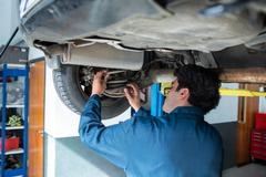 Mechanic repairing suspension of a car Stock Photos