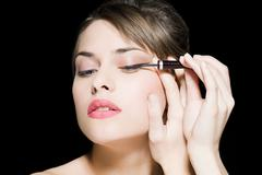 Woman applying eyeliner Stock Photos