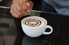 Barista decorate top surface of latte art coffee in white cup Stock Photos
