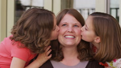 Daughters kiss mom on cheeks - stock footage