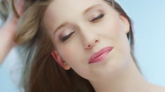 Attractive blonde woman is playing with her hair - stock footage
