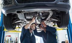 Mechanics examining silencer of a car using flashlight Stock Photos