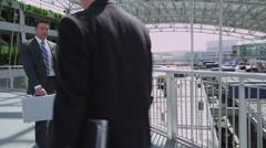 Business people walking across sky-bridge Stock Footage