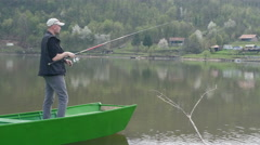 Fisherman with cap standing on green boat, holding rod and catching fish on lake Stock Footage