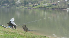 Fisherman sitting on lake coast and fishing with two rods. Stock Footage